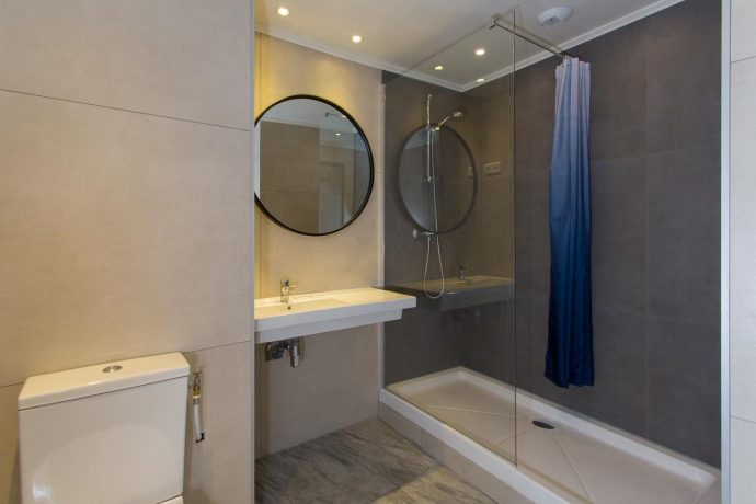 A clean bathroom with large mirror and walk in shower, stay with Villa Hostels, Nice.