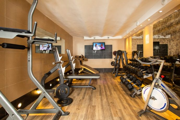 A gym room with free weights, bikes and gym equipment in a hostel in Nice, France