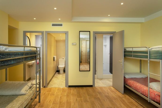 A large dormitory in a hostel with en suite bathrooms and bunk beds