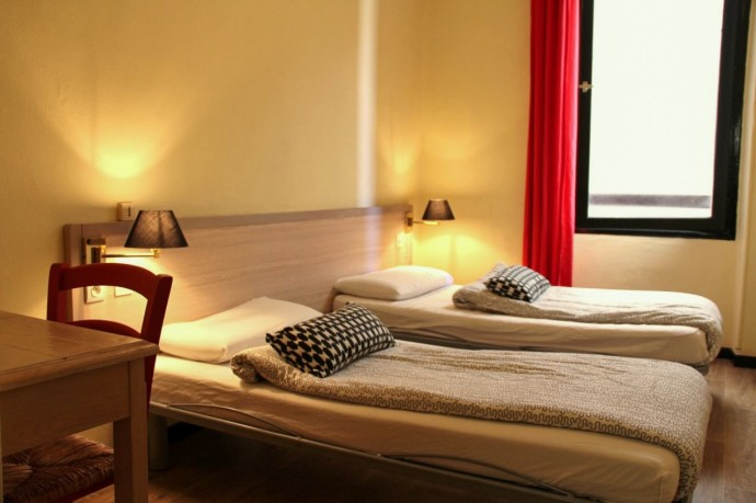 Twin room with bedside lamp and red curtain, comfortable hostel accommodation