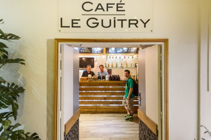 The open doors of the entrance to cafe le guitry, a hostel cafe bar in France