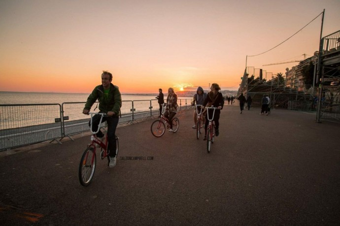 People walking and cycling along a promenade at sunset