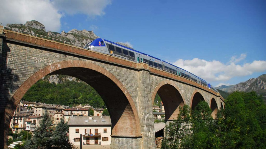 A train on a bridge in the mountains of southern France