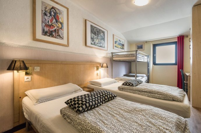 A clean, four bedroom dormitory with pictures on the wall at our Nice Hostel