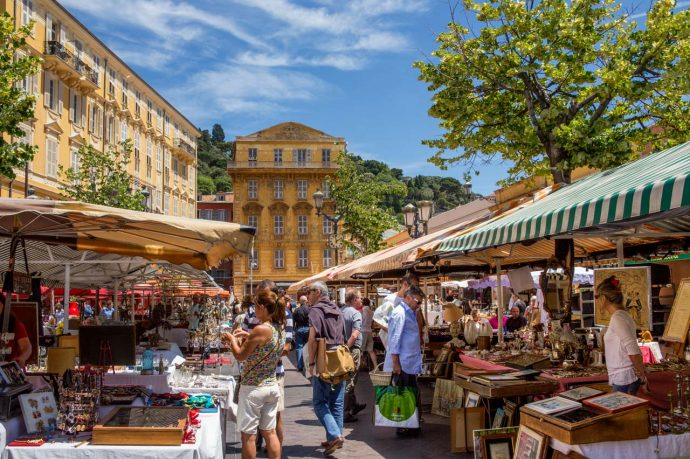 A busy colourful street market in the old town of Nice, France. People browsing stalls with local produce.