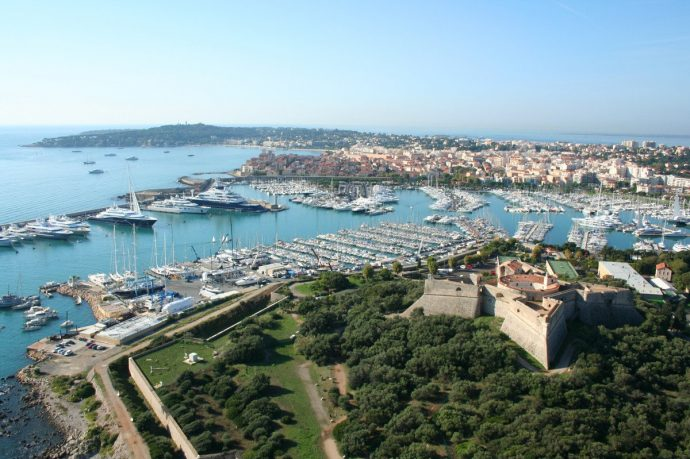 A pretty view over Antibes, over the castle to the port with sailing boats and a blue sea