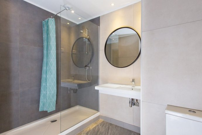 A new bathroom with a large mirror and walk in shower, green shower curtain
