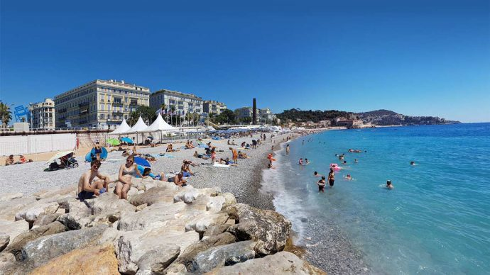 People enjoying a sunny day on the beach in Nice, France