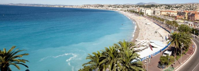 A long beach with a promenade lined with palm trees at the edge of Nice town