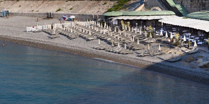 Un restaurante de playa con tumbonas y sombrillas en una playa de piedra