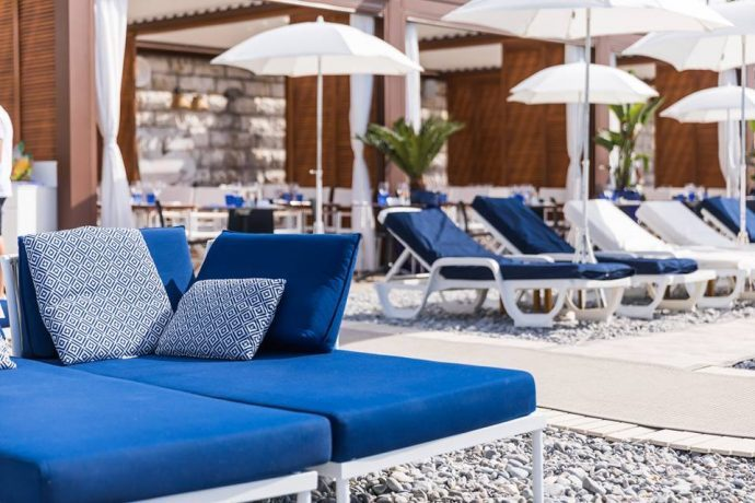Blue sun loungers and umbrellas on a pebble beach, best beaches in Nice