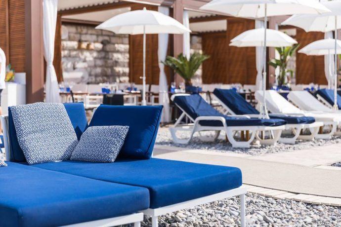 Lettini e ombrelloni blu su una spiaggia di sassi, le migliori spiagge di Nizza