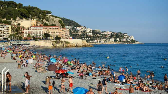 A bustling beach in Nice, France. People enjoying the sun and playing in the sea