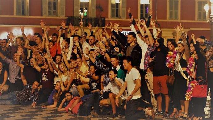 Large group of people in a town square posing for a photo