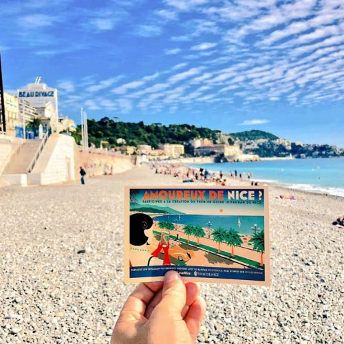 A view of Nice beach on a sunny day, a person holds up a vintage postcard