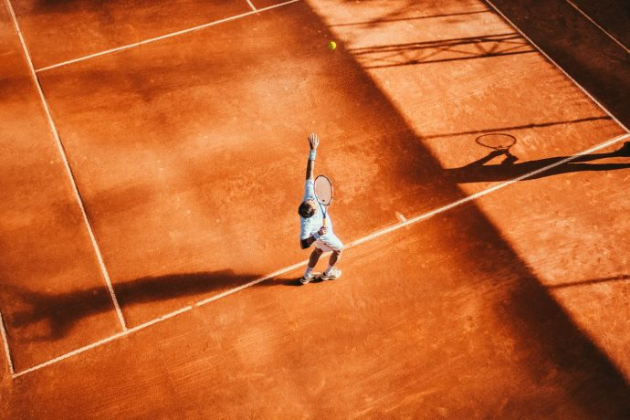 A tennis player serving on the terracotta court, Nice tennis boot camp