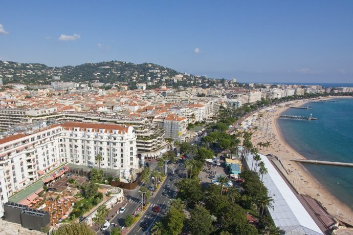 An Aerial view of the beach and town of Cannes with green trees and Azure sea