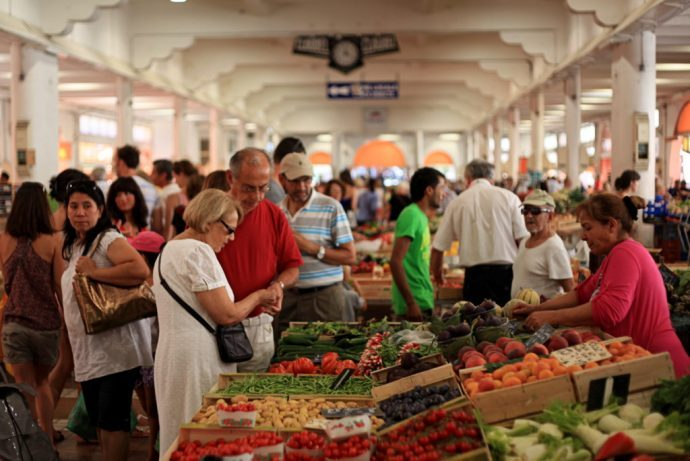 Fruit, vegetables, cheese, herbs laid out in a busy food market in Cannes