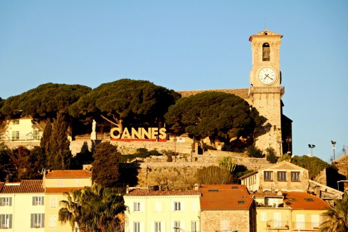 The clocktower and colourful houses in Cannes town at Sunset