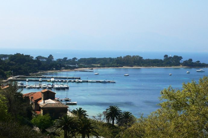 The long sweeping bay of the Lérins with a beach and moorings with boats, lined by green trees