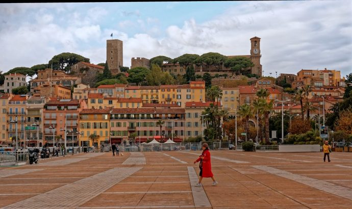 A woman in red walking across a plaza in front of old historic buildings of Cannes