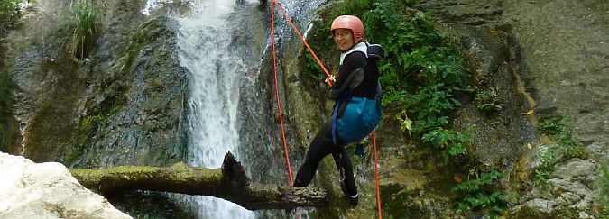 A woman in a red safety helmet standing on a log over a river holding a rope