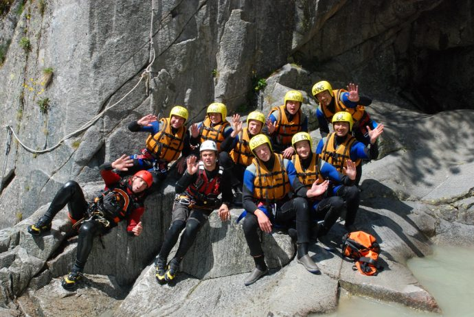 A group of people with canyoning equipment and safety helmets