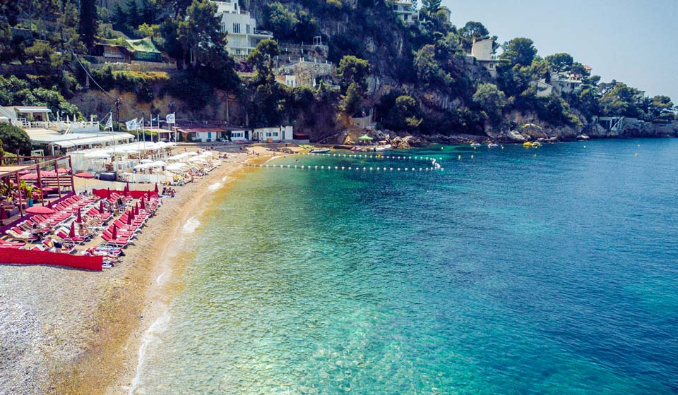 Cap D'Ail beach, a beautiful bay with Azure sea with a pretty restaurant, one of the top ten beaches on the French Riviera,