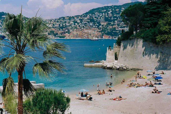 A picturesque sandy beach with people enjoying the sea at Cap Ferrat, Passable beach