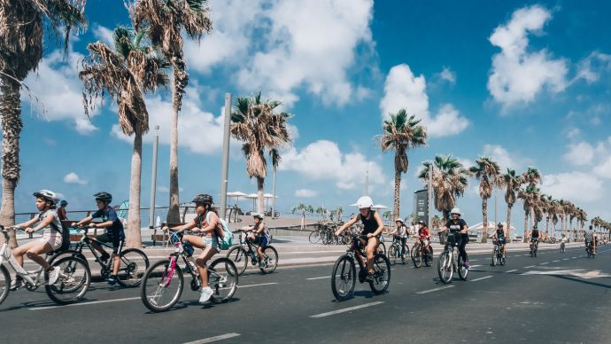 A group of young people wearing safety helmets cycling along the promenade in Nice with blue sky and palm trees in the background