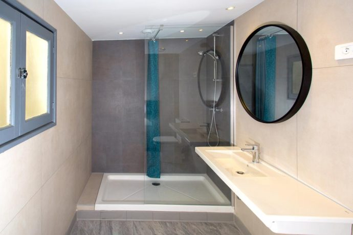 New bathroom with walk in shower, sink and large mirror