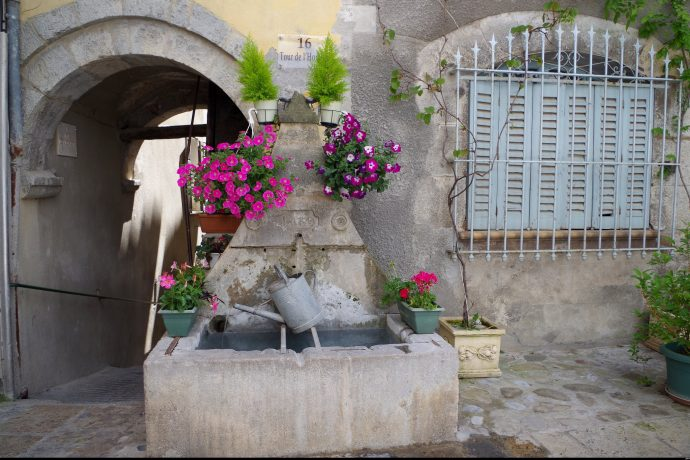 A fountain with colourful flowers in medieval street