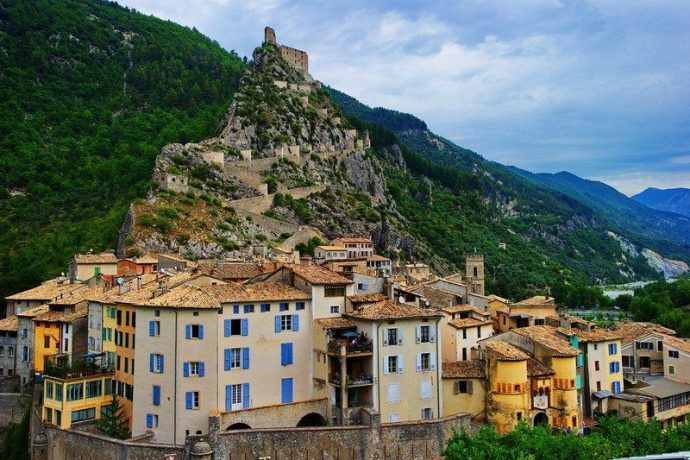 Colourful old houses on a mountain side leading up to a castle