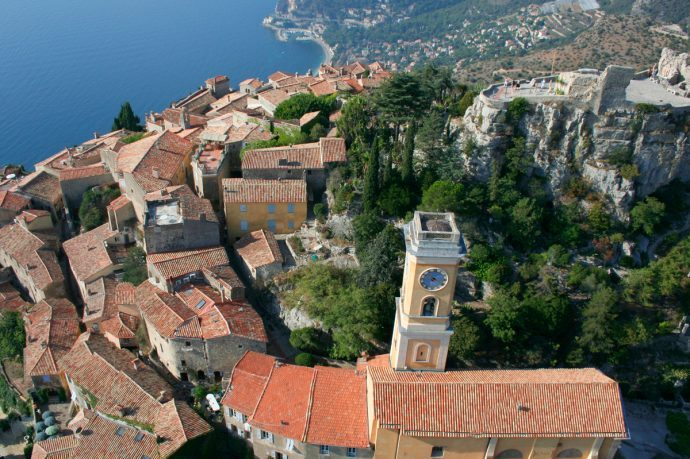 Aerial view of Eze village with old building and a church spire leading out to the sea