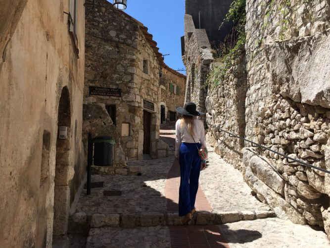 A girl walking up an old town stone street in Eze village in the South of France
