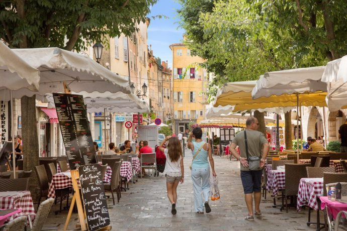 A couple walking through a colourful, pretty town square in Grasse, lined with restaurants