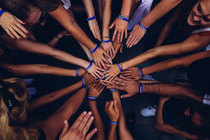 A group of people with blue wrist bands all putting their hands together in a circle