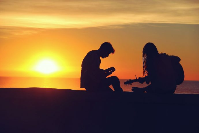 boy and girl playing guitar sunset music group