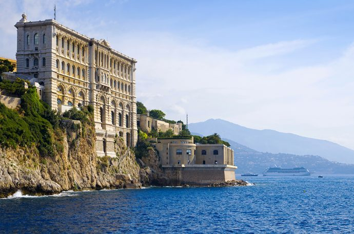 The tall neoclassical building of the Oceanographic Museum of Monaco built on a the rocky coastline at the edge of the sea