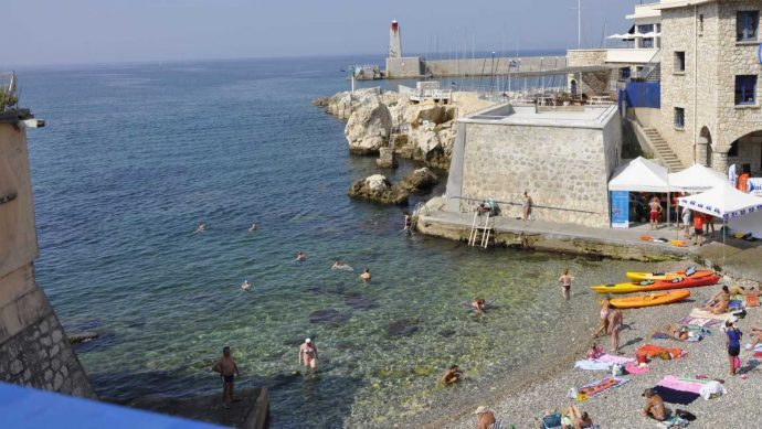 A small secluded beach with a harbour wall, people are sunbathing and swimming