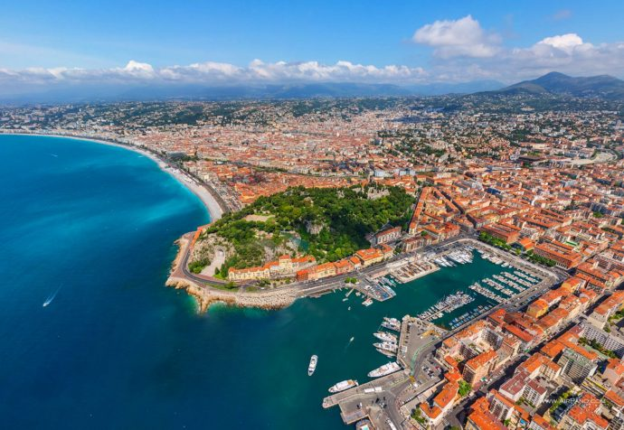 A view of Nice from above, looking along the coast and at the old town on a sunny day, with a beautiful blue sea and red Roofs
