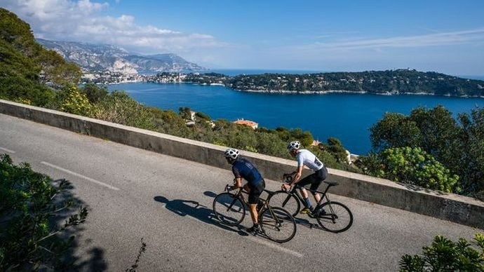 Two people cycling along a coastal road with the sea in the background