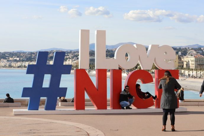 People posing in front of the #ILoveNICE sign with Nice beach in the background