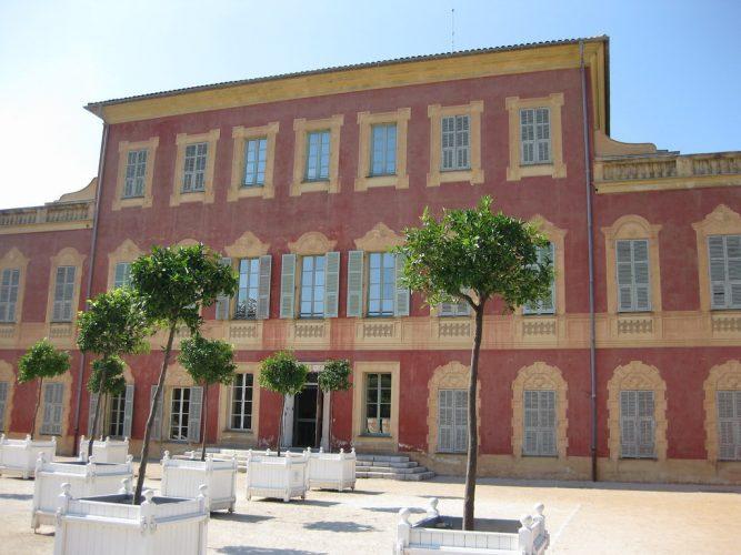 A fachada vermelha do museu Matisse, um belo edifício com janelas fechadas com árvores do lado de fora