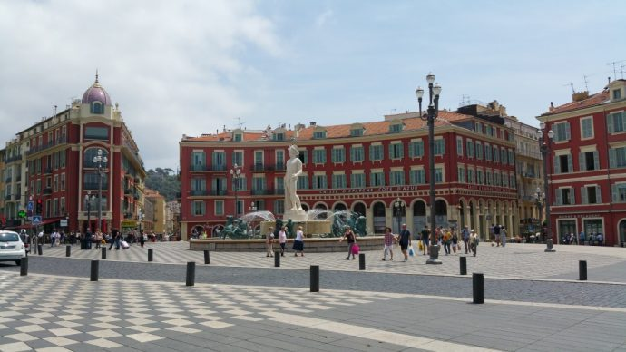 The fountain at Place Massena lined with traditional red buildings, Nice culture, France
