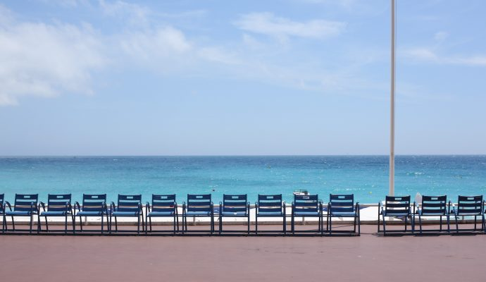 Blue chairs facing the azure sea on a sunny day on the Promenade des Anglais