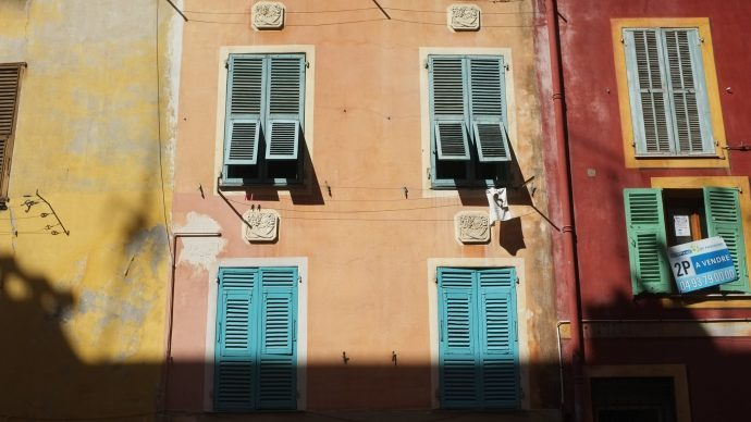 An orange facade with turquoise french shutter in the old town of Nice