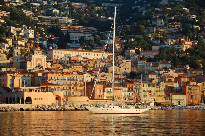 A boat at sunset at the port of Villefranche, with pretty coloured buildings in the background