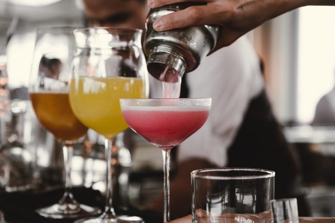 Pouring colourful cocktails from a shaker into cocktail glasses
