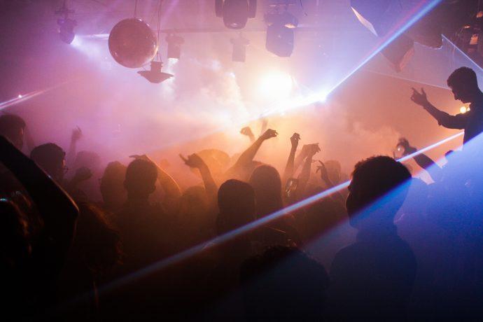 Gente bailando con humo y luces de colores en un club nocturno de Niza